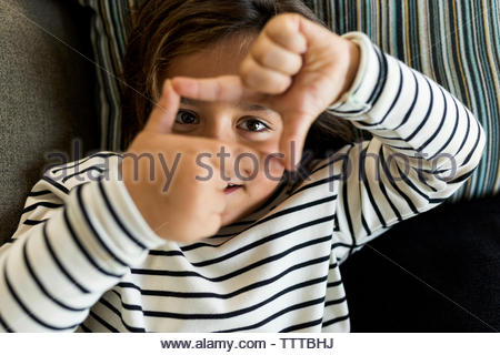 Cute little boy with striped top making a rectangle with his hands - Stock Photo