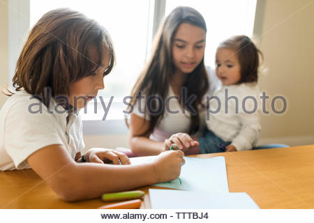 Nanny baby sitting  2 siblings doing home work at home - Stock Photo