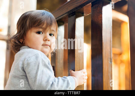 Happy confident curious little girl on balcony - Stock Photo