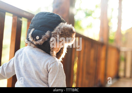 Happy little girl with hat on veranda - Stock Photo