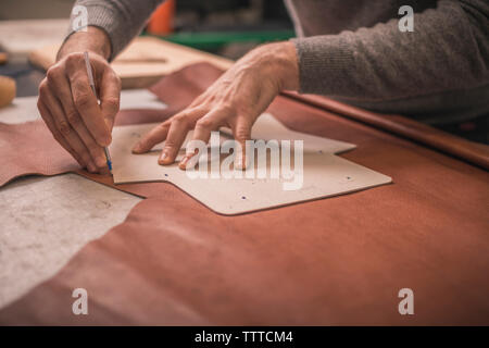 Midsection of shoemaker measuring leather with cardboard at workshop - Stock Photo