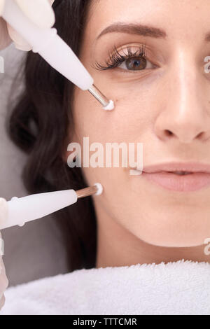 Portrait of confident patient having beauty treatment by female doctor at medical clinic - Stock Photo