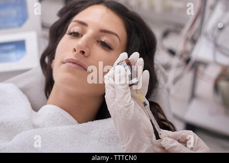 Cropped hands of female doctor filling botox injection while patient lying at medical clinic - Stock Photo