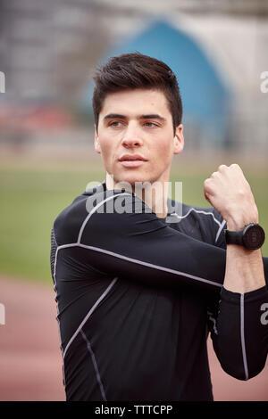 Male athlete exercising on sports track - Stock Photo