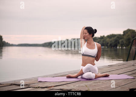 Confident woman with eyes closed practicing cow face pose on pier by lake against sky during sunset - Stock Photo
