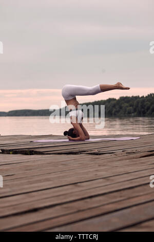Side view of woman practicing headstand on pier by lake against cloudy sky during sunset - Stock Photo