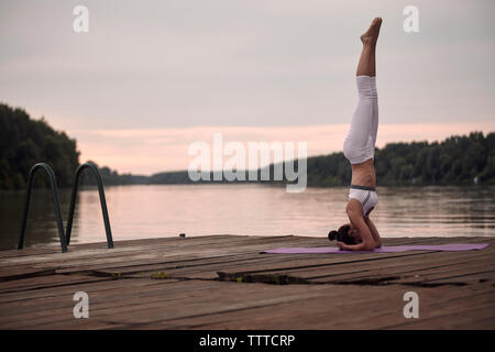Woman practicing headstand on pier by lake against cloudy sky during sunset - Stock Photo