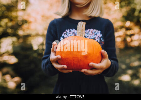 Midsection of girl holding pumpkin at field - Stock Photo