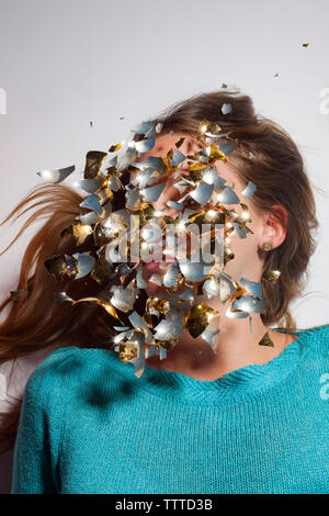 Digital composite image of woman's face covered with glass pieces on white background - Stock Photo