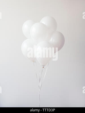 Bunch of balloons against wall - Stock Photo