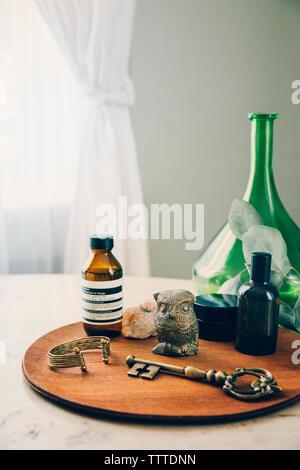 High angle view of objects arranged on wooden board by flask - Stock Photo