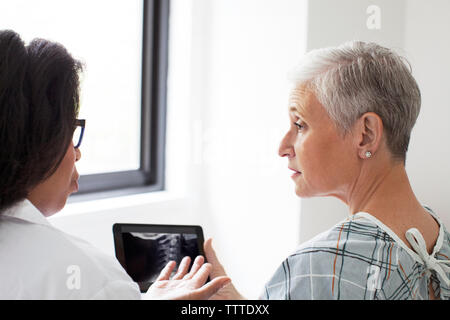 Female doctor discussing X-ray image with patient in hospital - Stock Photo