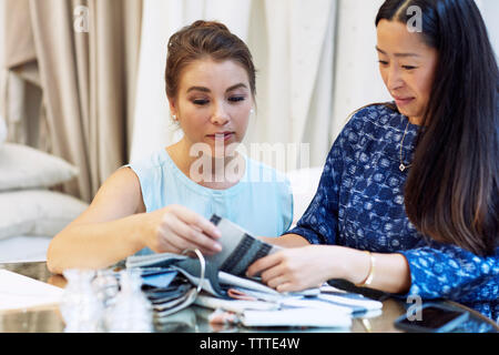 Interior designers looking at fabric swatches while sitting in workshop - Stock Photo