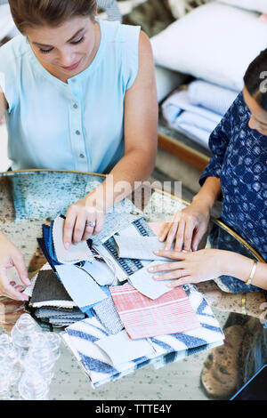 High angle view of interior designers looking at fabric swatches while working in workshop - Stock Photo