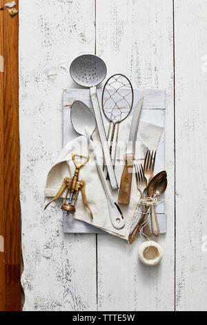 High angle view of kitchen utensils with corkscrew and thread on wooden table - Stock Photo