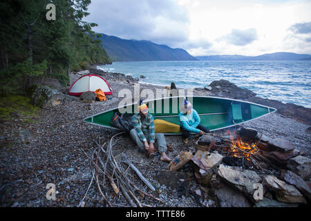 Couple sitting by campfire while canoe camping on Lake Pend Oreille.