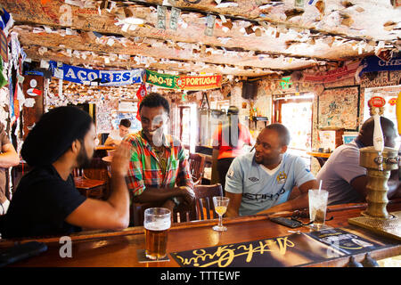 BERUMDA. Chef Marcus Samuelsson having a drink with the locals while watching a soccer game at the Swizzle Inn at Bailey's Bay. - Stock Photo