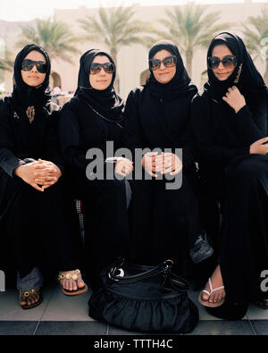 OMAN, Barr Al Jissa Resort and Spa, Muslim women sitting side by side in traditional clothing. - Stock Photo