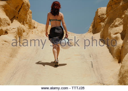Rear view of woman in bikini holding helmet while walking on hill at desert against clear sky during sunny day - Stock Photo