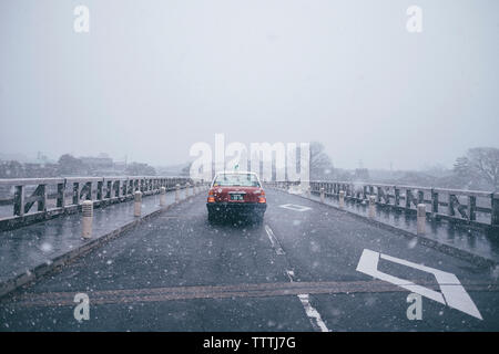 Car on road against clear sky during snowfall - Stock Photo