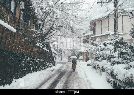 Rear view of woman holding umbrella while walking on snow covered road during snowfall in city - Stock Photo