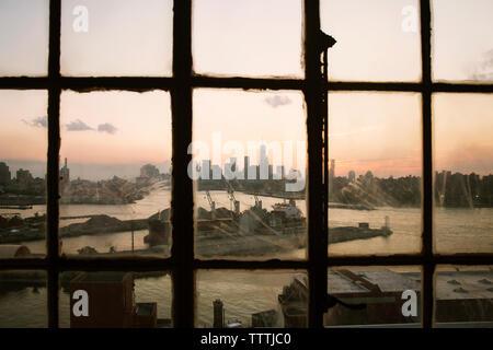 City skyline and harbor seen through glass window - Stock Photo