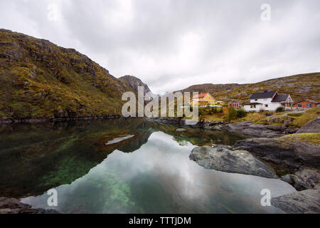 Houses and mountains by calm lake against sky - Stock Photo