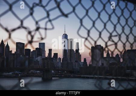 One World Trade Center seen through broken chainlink fence - Stock Photo