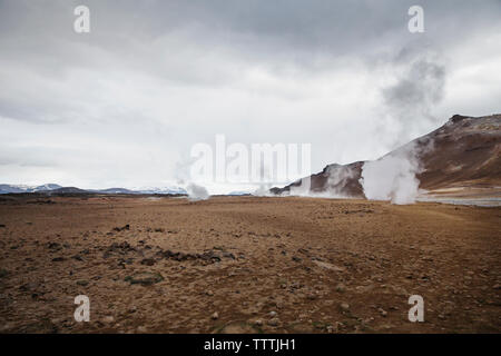 Steam rising from geysers against sky - Stock Photo