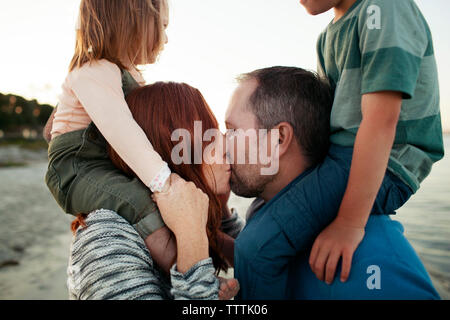 Parents kissing while carrying children on shoulders at beach - Stock Photo