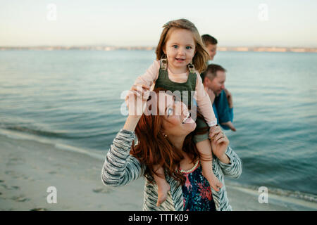 Cheerful parents carrying children on shoulders at beach against clear sky - Stock Photo