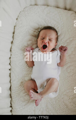 Overhead view of baby girl yawning while lying in crib - Stock Photo