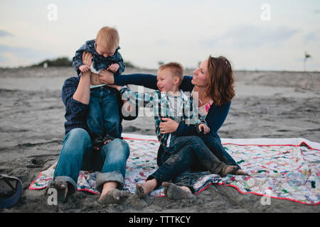 Happy family sitting on blanket at beach - Stock Photo
