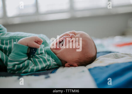 Close-up of baby boy yawning while sleeping on bed at home - Stock Photo