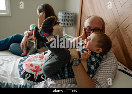 Playful family enjoying on bed at home - Stock Photo
