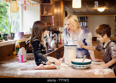 Family playing with flour in kitchen - Stock Photo