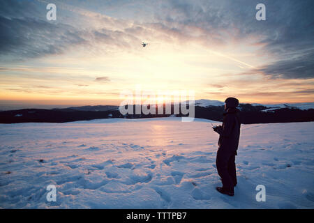 Man flying drone in sky while standing on snowy mountains - Stock Photo