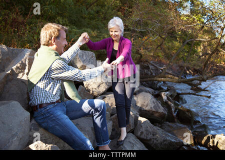 Couple on rocks at lakeshore - Stock Photo