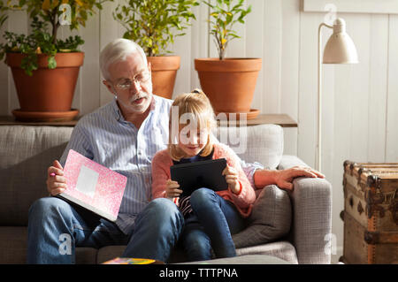 Girl using tablet computer while sitting with grandfather on sofa at home - Stock Photo