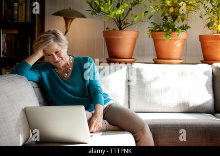 Woman with hand in hair using laptop computer while sitting on sofa at home - Stock Photo