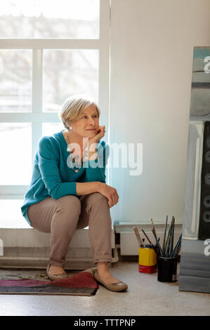Thoughtful woman looking away while sitting on window sill - Stock Photo