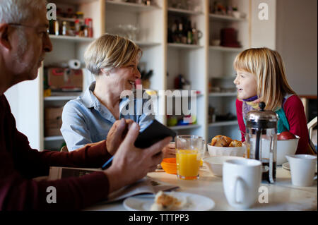 Grandfather looking at granddaughter talking to grandmother while sitting at table - Stock Photo