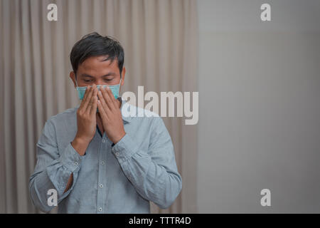 Male businessman who closes the protective mask Due to illness and cough - Stock Photo