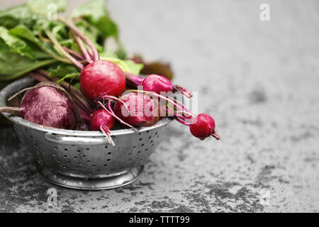 Bunch of fresh beets in a colander on grey background - Stock Photo