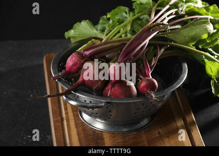 Bunch of fresh beets in a colander on wooden board - Stock Photo