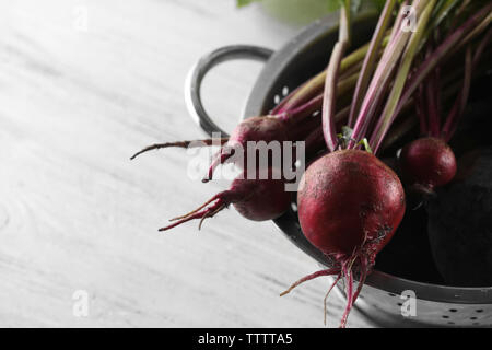 Bunch of fresh beets in a colander on light wooden background - Stock Photo