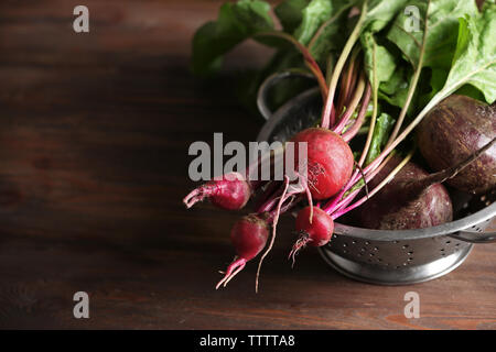 Bunch of fresh beets in a colander on wooden table - Stock Photo