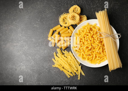 Plate with different kinds of dry pasta on table - Stock Photo