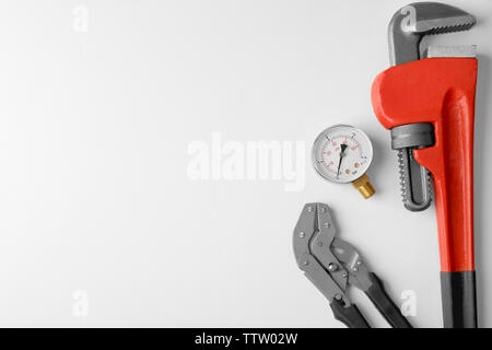 Plumber tools with red wrench isolated on white - Stock Photo