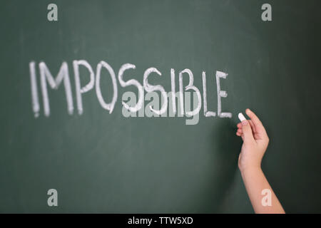 Little girl writing word impossible on chalkboard - Stock Photo